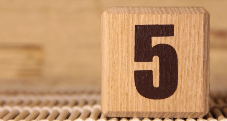 A wooden cube with the number five printed on it.