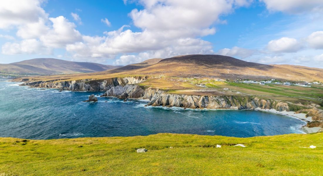 Achill Island is pictured. There is clear blue water on the left, and rolling green hills on the right. There is a blue sky with fluffy clouds interspersed.