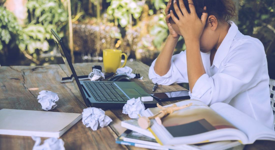A woman with her head in her hands in front of a laptop at a table covered in scrunched up balls of paper.