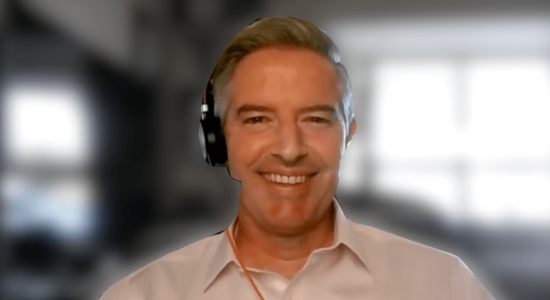 A headshot of Mark Nolan smiling at the camera with a headset on.