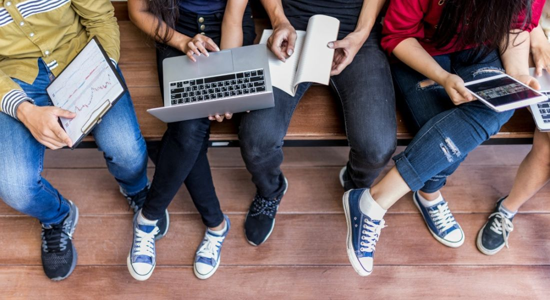 Five college students pictured from the shoulders down, seated on a wooden bench with laptops and notepads.