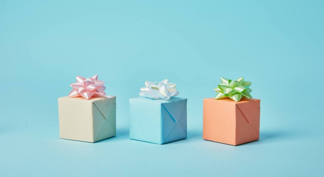 Three gift parcels with bows on top of them are sitting against a blue background.
