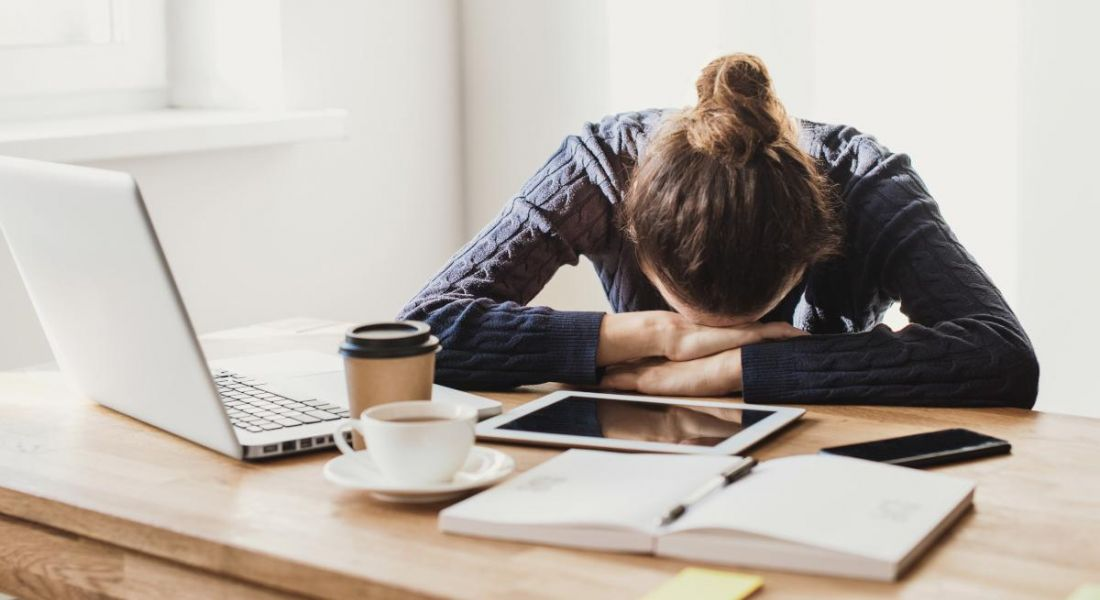 A woman slumped with her head on her arms at a desk. In front of her is a laptop, numerous documents and a coffee cup.