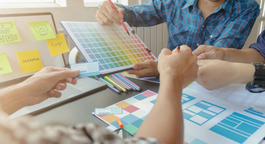 A group of people sit around a table, picking out colours and features to design a website.