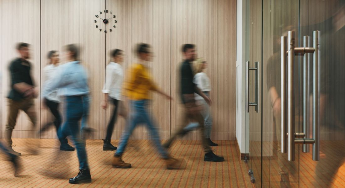 A motion-blue image of a group of people walking into an office.