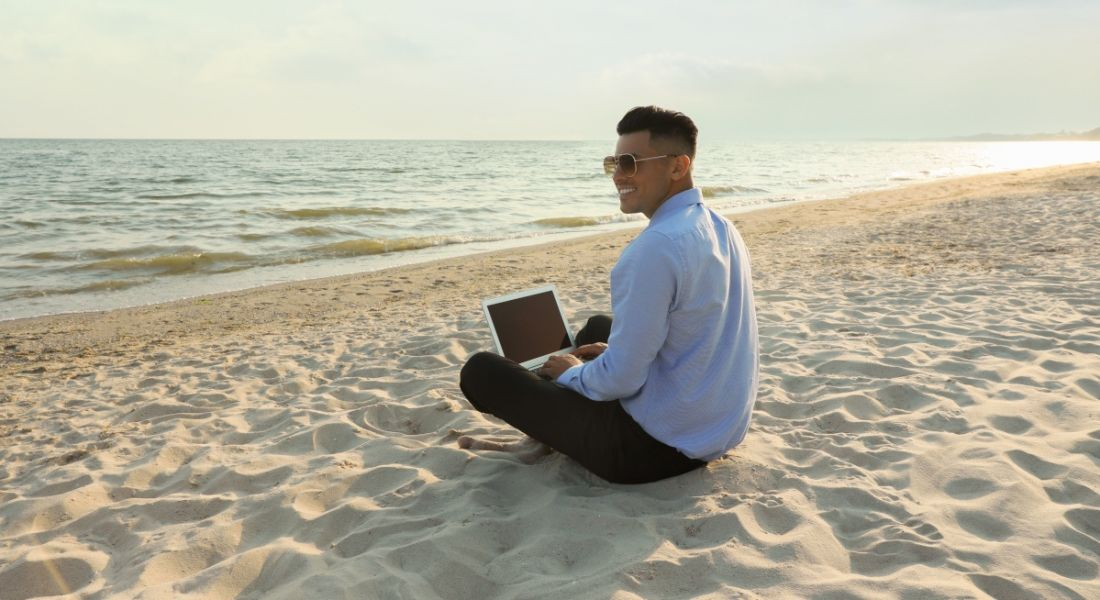 Happy businessman sits cross-legged working with a laptop on the beach.
