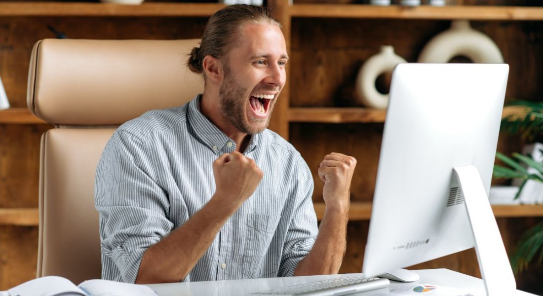 Happy worker sitting at a desk in a modern office rejoicing, raising his fists and yelling at the computer.