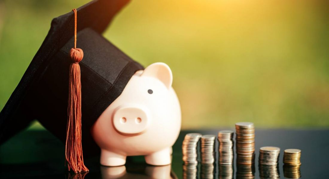 Piggy bank with a graduation cap on it, beside some stacks of coins.