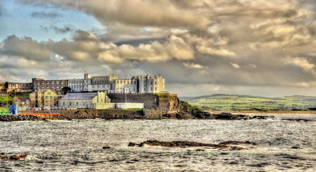 A view of the coast of Portstewart on a cloudy day. Buildings can be seen on a cliff overlooking the Atlantic Ocean.