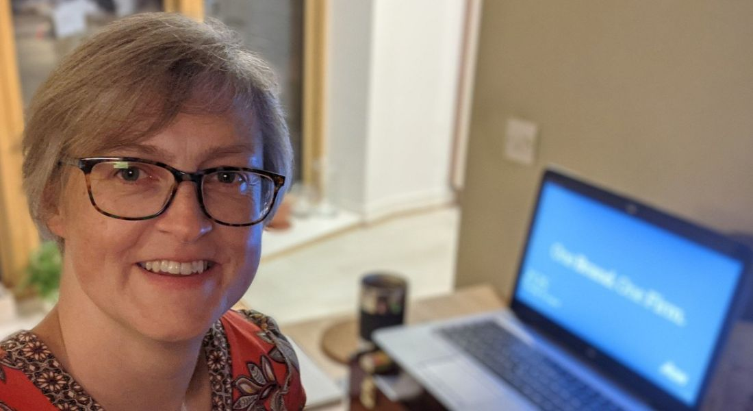 A woman with glasses smiles at the camera while her laptop sits on a desk in the background as she is working from home.