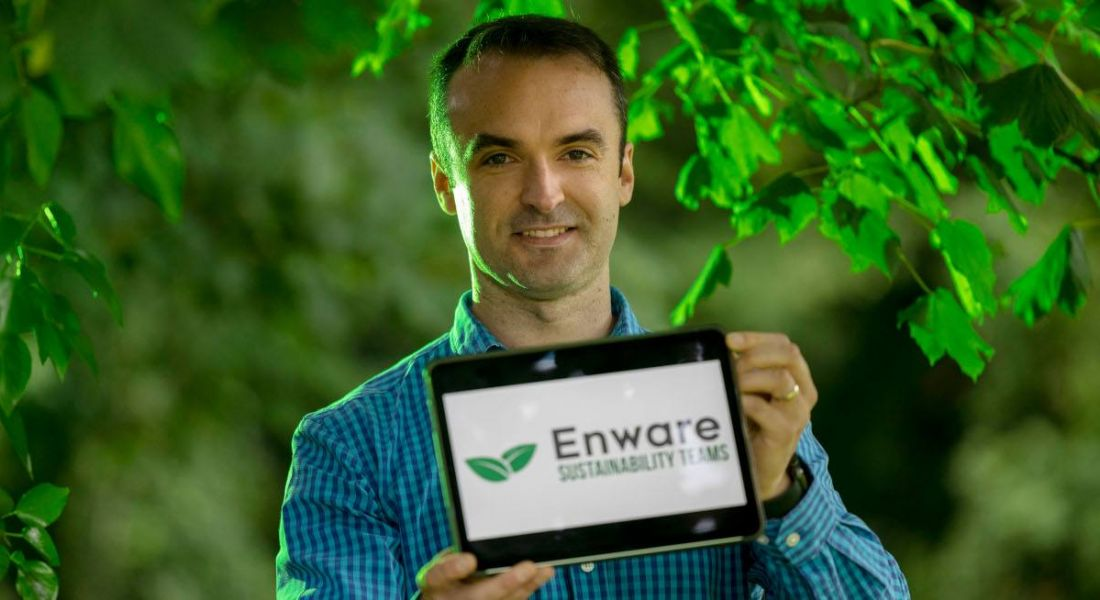 John Keohane pictured holding a tablet device with the Enware logo on the screen, standing against a background of trees with bright green leaves.