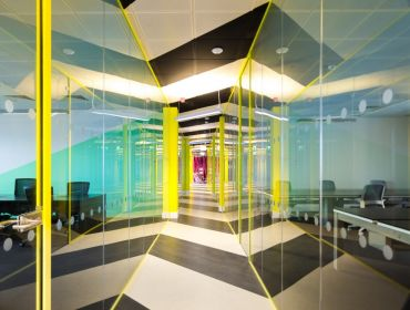 A long glass corridor with yellow lights around the edges. Through the glass is a co-working space for hybrid working.