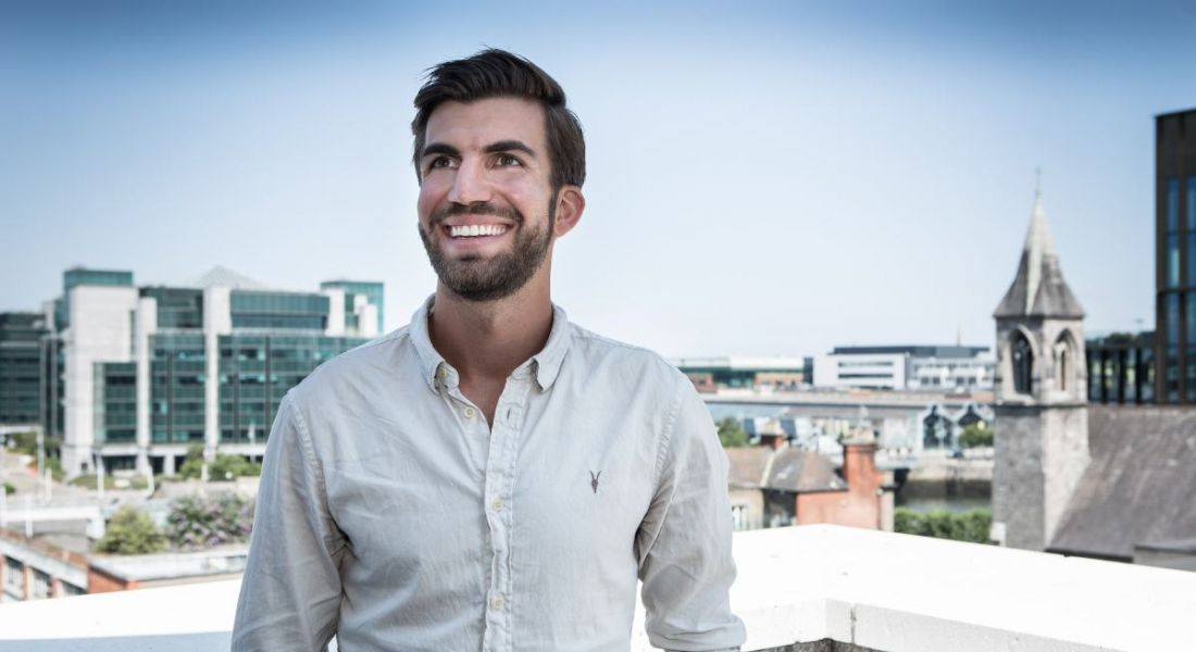 A man in a casual white shirt stands outside with a vast cityscape behind him in the background. He is Hanna Renner, CEO of Personio.
