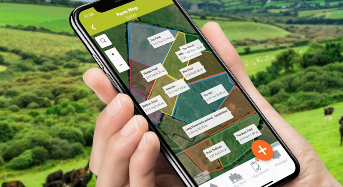 Hand holding a smartphone displaying the Herdwatch farm management app with green fields in the background.