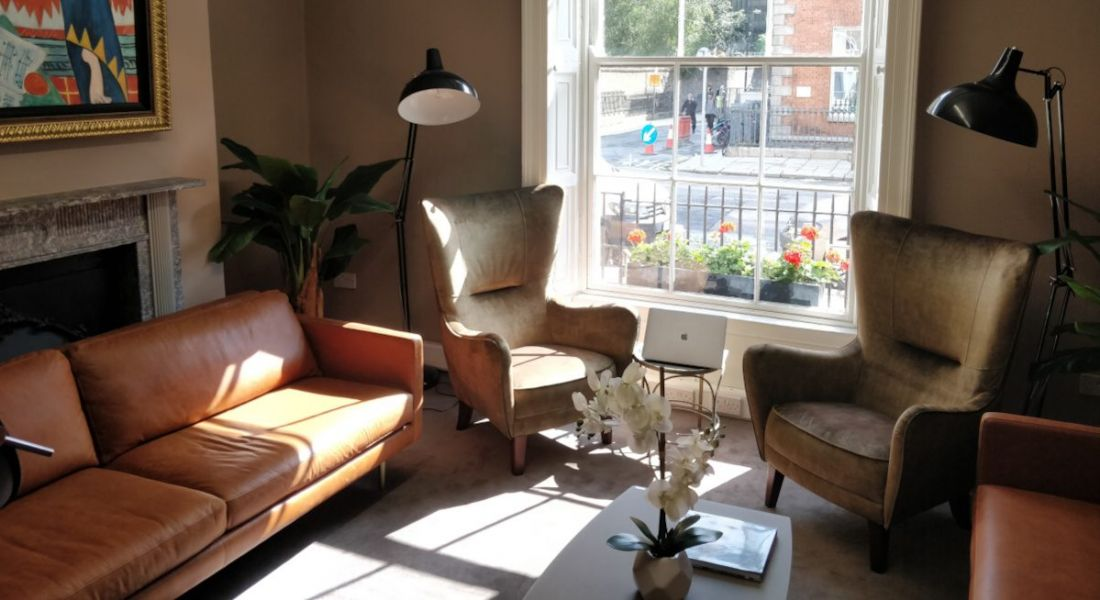 Thrive Global's Dublin office, featuring couches in a ground floor conference room and a view of Mount Street Upper.