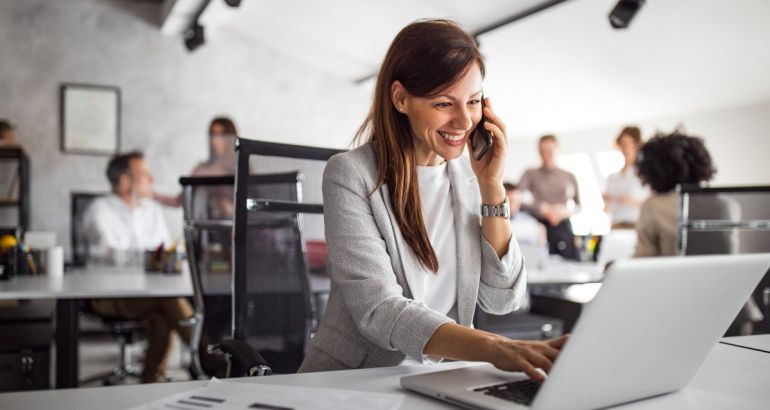 A woman in business attire smiles with a phone up to her ear while working on a laptop. She is leading a team remotely.