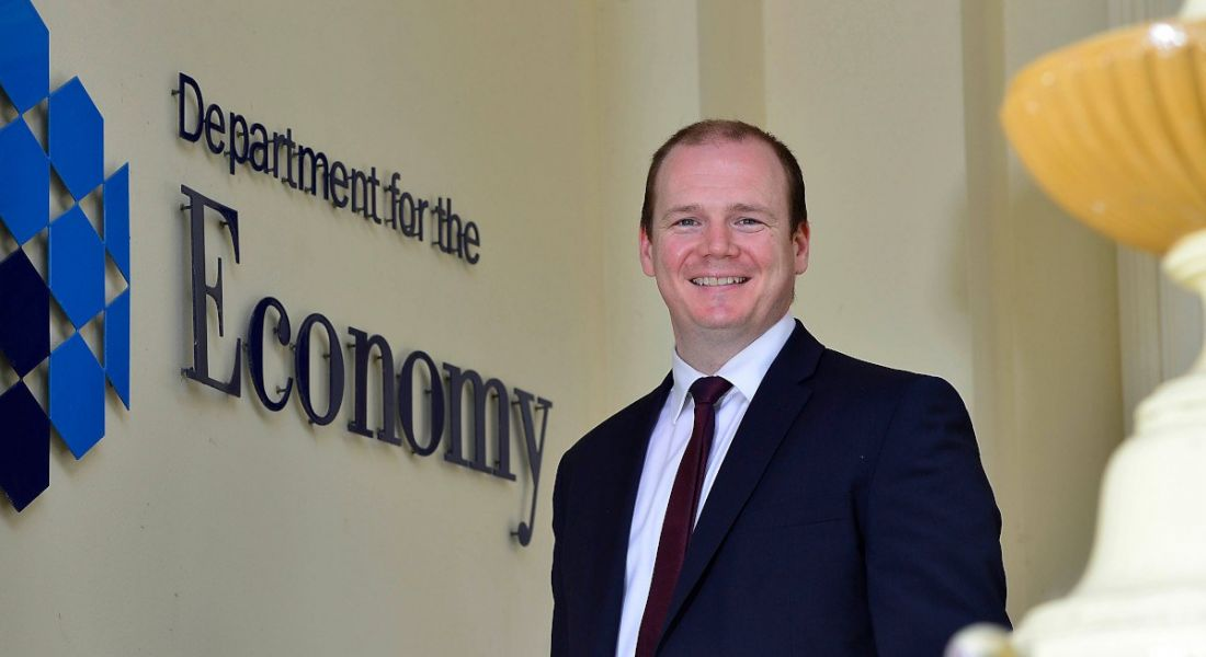 Northern Ireland economy minister Gordon Lyons stands alongside a wall with lettering that says department for the economy.