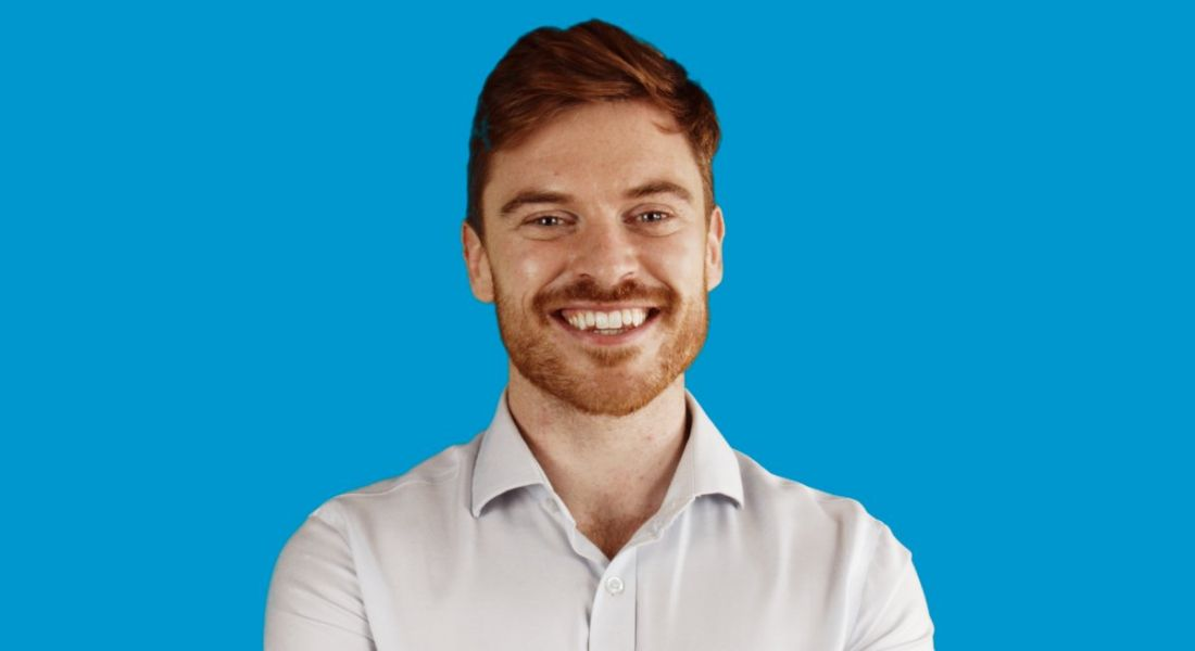 TJ Hegarty, founder of online tutoring business Breakthrough Maths pictured against a blue background.