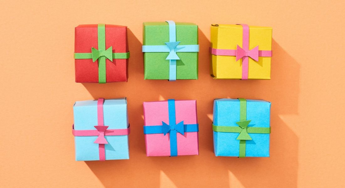 Six different coloured gift boxes lined up in two rows of three against an orange background, representing office perks.