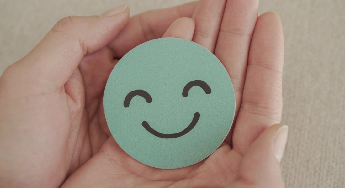 A pair of hands holding a round, blue piece of paper with a smiley face on it.