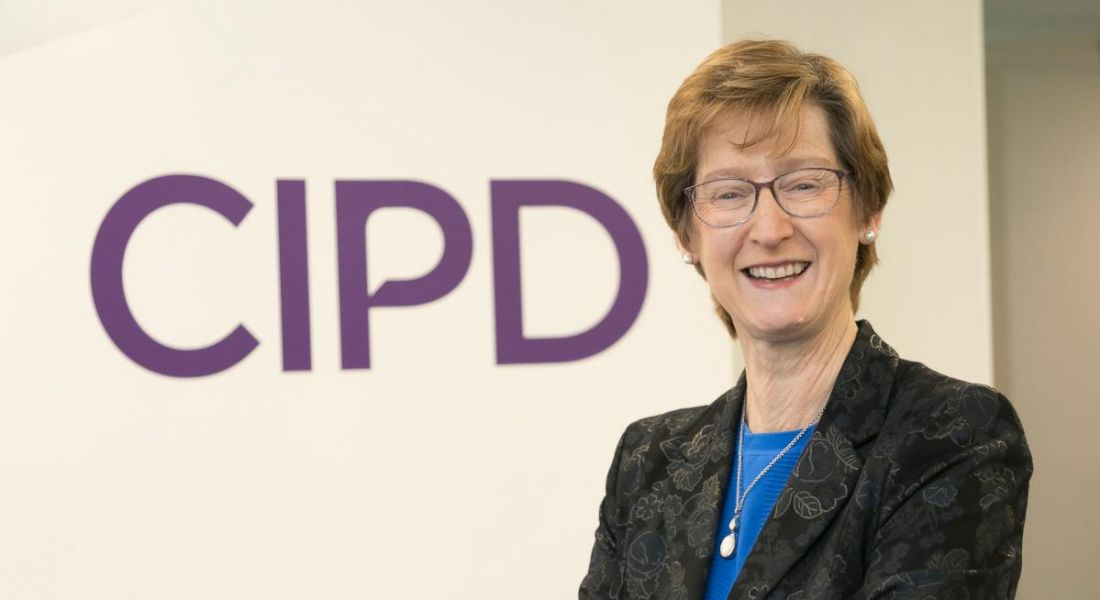 A woman with short hair wearing a black blazer with arms folded smiling at the camera in front of a wall that says CIPD in purple lettering.