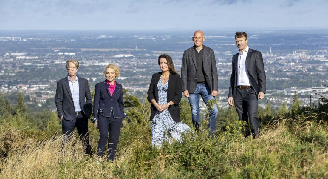 Five people stand on a hill with a view of Dublin behind them.