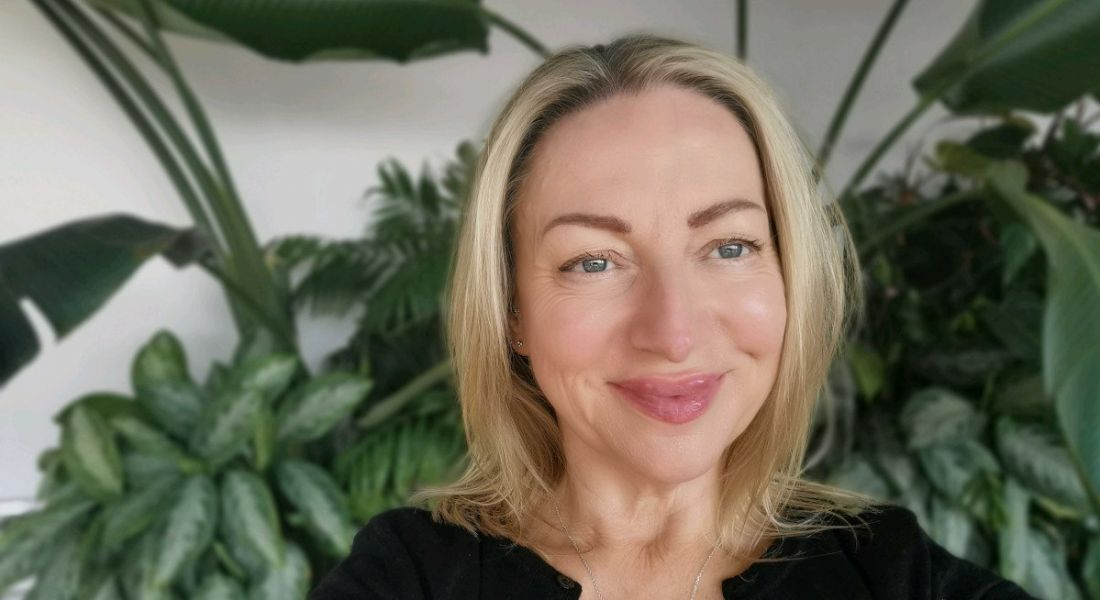 A headshot of a blonde woman smiling at the camera with some large, leafy indoor plants behind her.