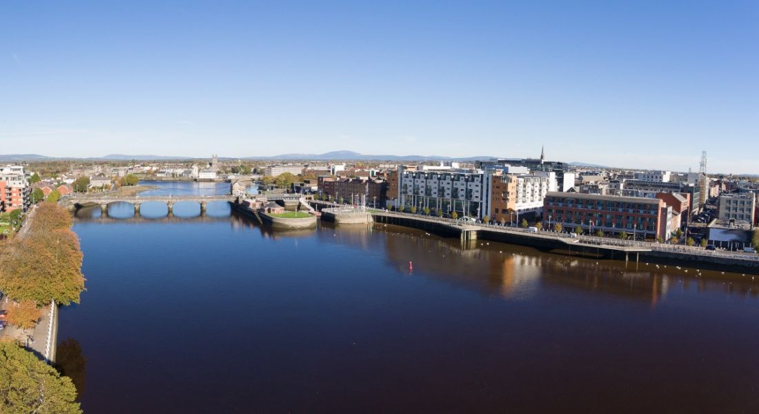 A wide-angle view of the Limerick city skyline against a clear blue sky and alongside the River Shannon.