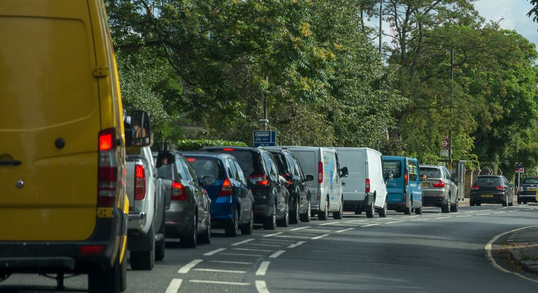 Commuters stuck in traffic on a tree-lined road.