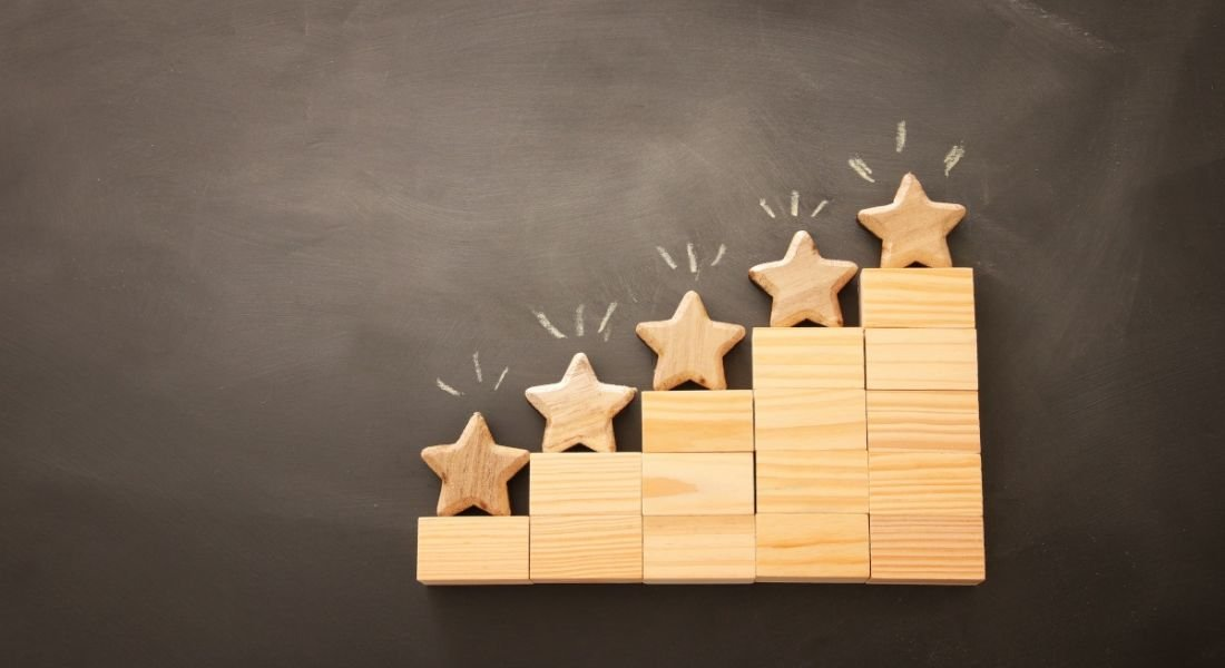 Wooden blocks stacked like a stepping system with wooden stars on top of each block like a ranking system.