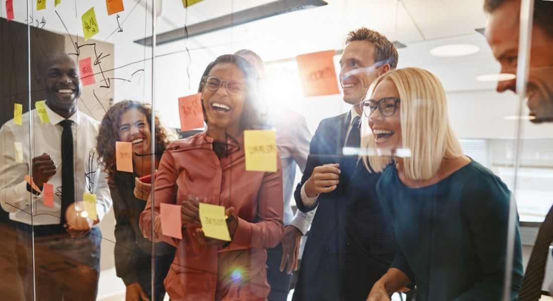 A group of happy business people having a very fun brainstorming session in an office with a glass wall and post-it notes all over it.