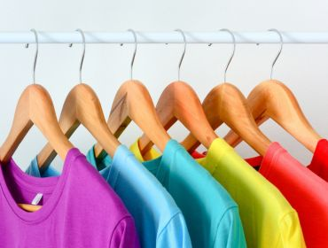 A row of T-shirts hanging on a rail in a rainbow of colours.