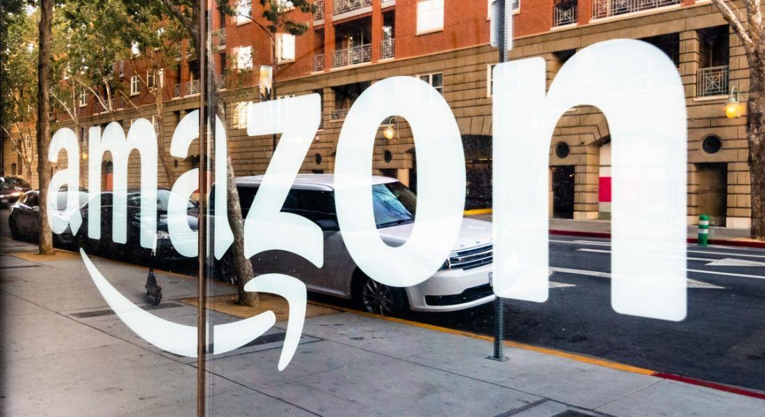 Amazon logo reflected in a glass shopfront window.