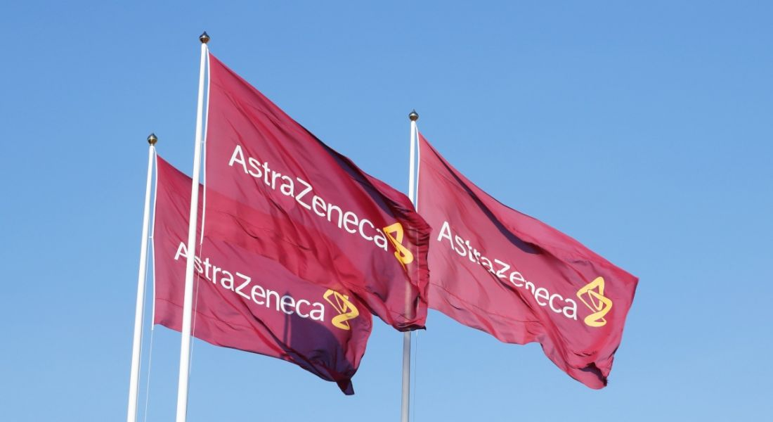 Three purple flags with the logo for Atrazeneca flying in the wind on top of flagpoles, against a clear blue sky.