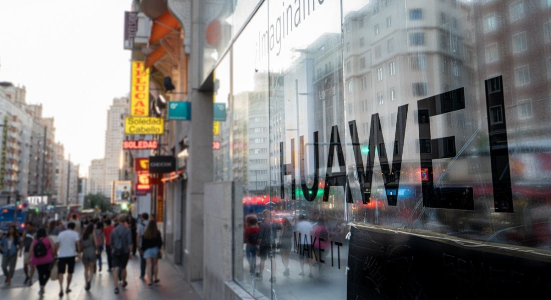 People walk past Huawei offices bearing the company name in a busy street.
