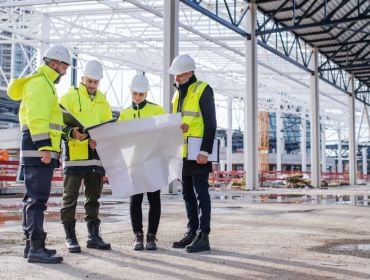 Group of four engineers gathered in a group standing at a building site preparing their engineering project notes.