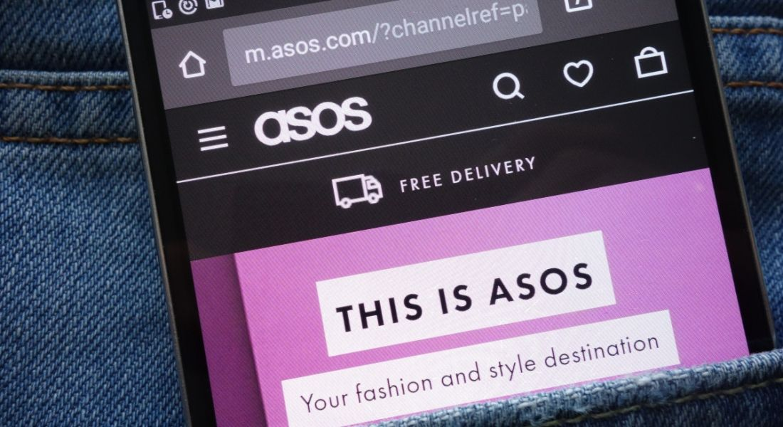 Smartphone displaying fashion retailer ASOS's webpage. The phone is in the pocket of a denim garment.