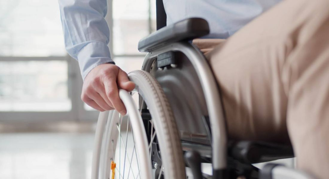 Close-up of a man's hand holding the wheel of his wheelchair as he enters an office.