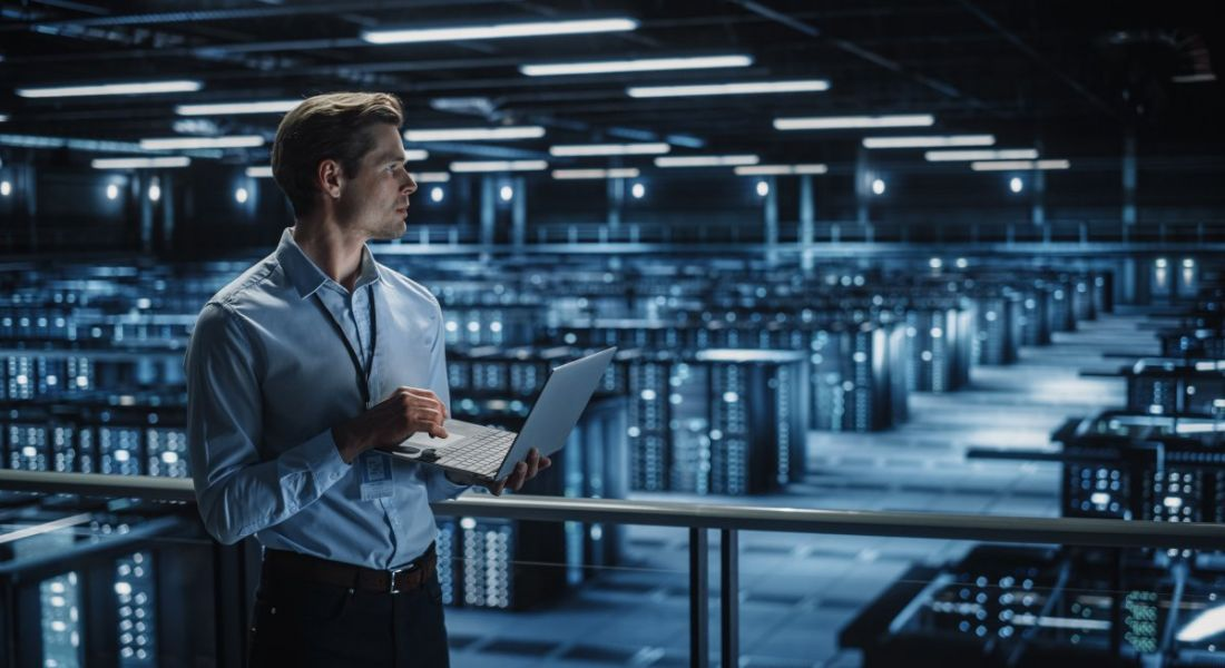 A man standing with a laptop in front of rows of servers.