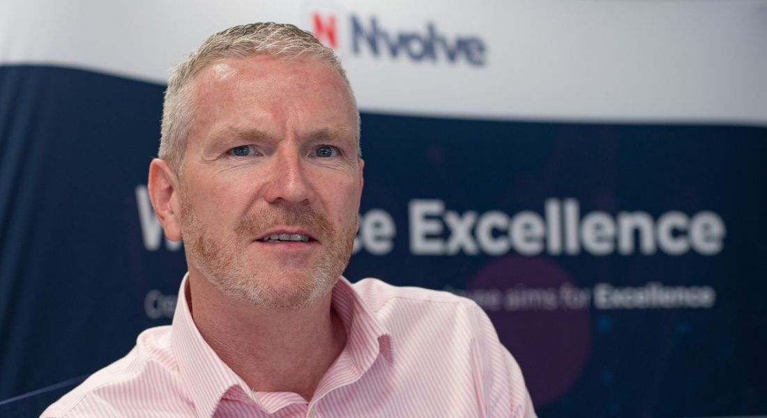Barry Harper pictured standing in front of a display featuring the Nvolve logo.
