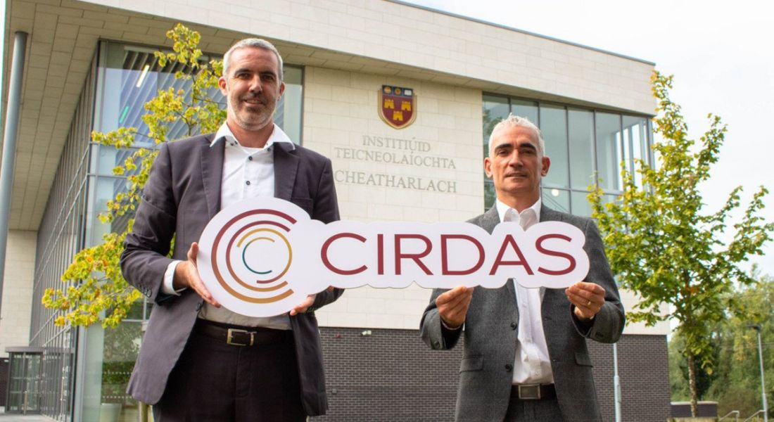 Two men stand outside IT Carlow, holding a sign that says 'CIRDAS'.