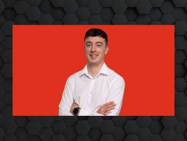 A headshot of Colin Hehir, a young man in a white shirt against a red background surrounded by a dark grey designed frame.