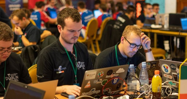 Three young men wearing black T-shirts working on computers in a busy hall. They are participating in a cybersecurity challenge.