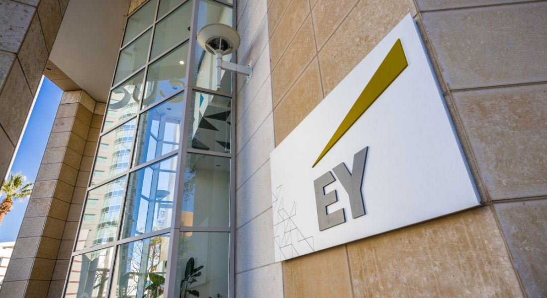 An EY logo on a white background on the side of a large office building on a sunny day.