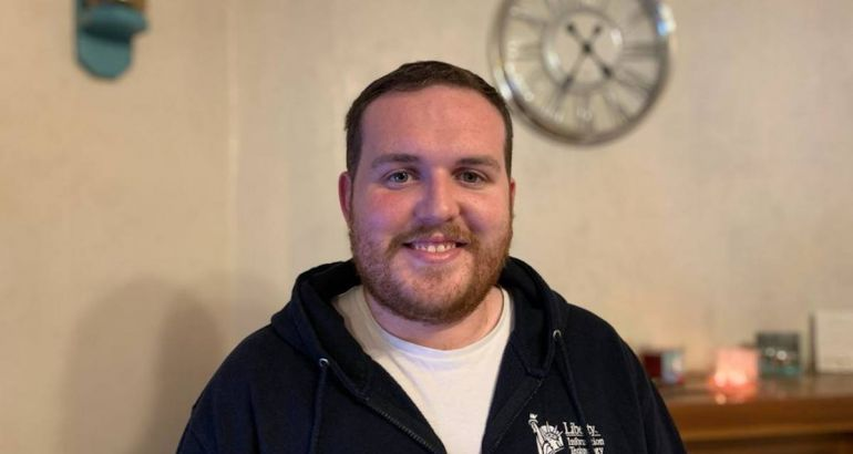 A young man with facial hair smiles at the camera. He is wearing a navy zip-up hoodie with a white Liberty IT logo on it.