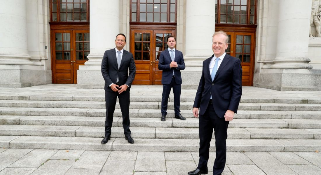 Three men in suits stand, socially distanced, on the steps of Government buildings.