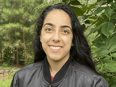 A close-up of a young woman, Jasmine Singh, who works at NASA as an intern. There are leafy trees in the background.