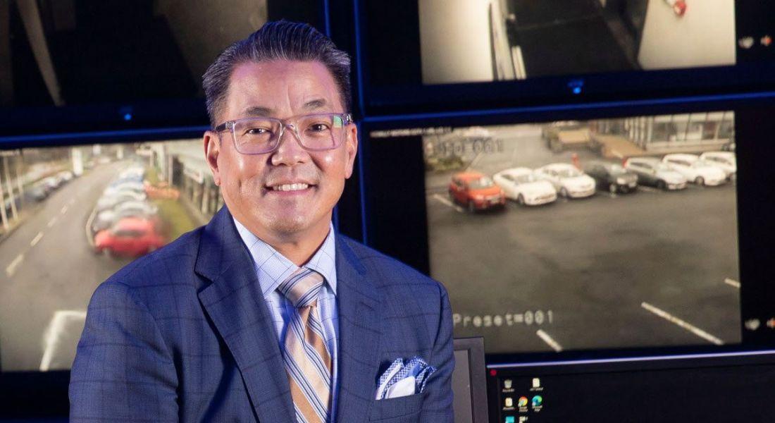 Kurt Takahashi headshot against Netwatch security camera background.