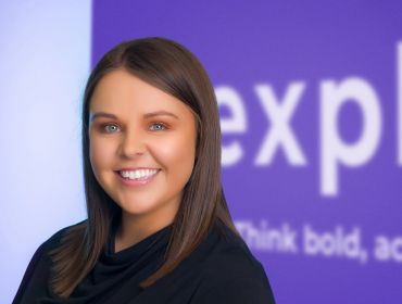 A young brunette woman smiling at the camera in front of a purple and white wall that says Expleo.