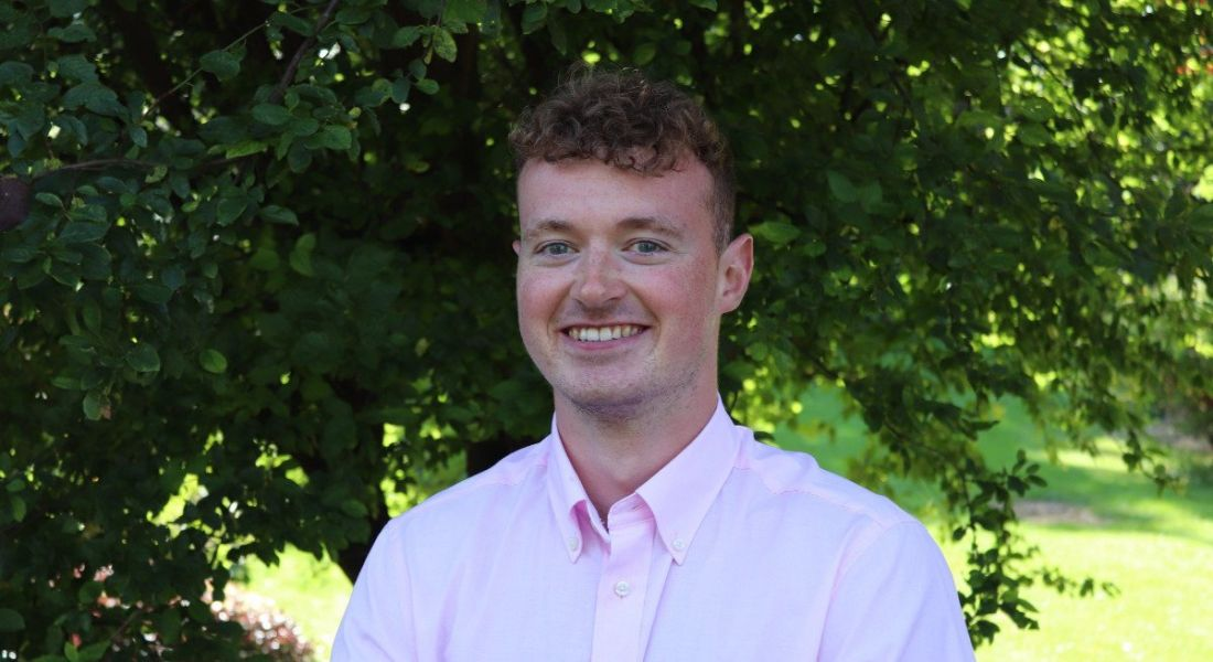 A young man wearing a pale pink shirt smiles at the camera against a backdrop of trees and foliage. He is a graduate working at Accenture.